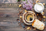 Rustic wooden background with cup of coffee, milk, bun with marzipan and lilac flowers. White vintage dinnerware and spoon. Breakfast at summer morning. Top view, place for text.