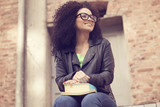 Happy afro woman smiling with books