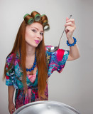 woman housewife with bowls and pans in a bathrobe and curlers Fu