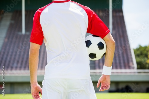 Mid section of football player standing with a ball