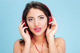Pretty young woman wearing headphones over blue background