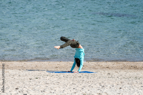 Poster Man doing yoga on the seashore. Young exercising at the beach.