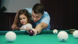 Dad teaches his daughter to play billiards. It shows how to hold the cue