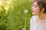 Lovely woman holding and blowing on dandelion outdoors - 113056780