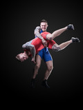 Two young freestyle wrestlers isolated on black background