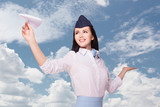 Charming Stewardess Dressed In blue Uniform. Sky With Clouds Background.Paper airplane.Model holding something on the palm.