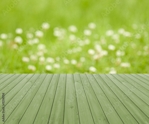 Empty wooden deck table with green and yellow soft focus background © mwstudio2