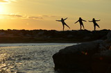 three women train by sunrise at sea