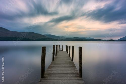drewniany-jetty-prowadzi-out-w-jezioro-z-dramatycznymi-chmurami