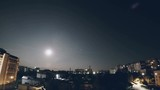 TIMELAPSE: Full moon in the night sky against the backdrop of the city, sleeping area.
