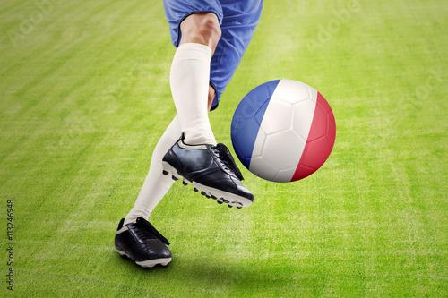 Poster Soccer player kicking a ball at field