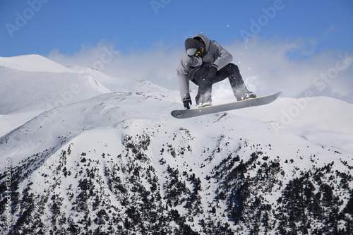 Snowboard rider jumping on mountains. Extreme freeride sport. Poster