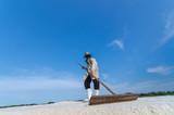 Worker is harvesting sea salt at salt field.