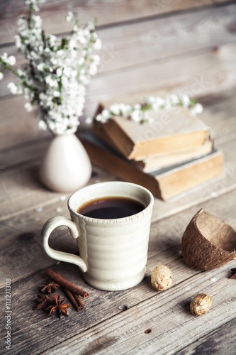 Large Cup of coffee on vintage wooden background. Spring flowers and books.