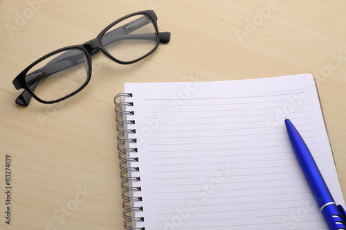 Poster Blank Note Book With Spectacle on Table
