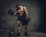 Full body portrait of bodybuilder with dumbbells in a studio.