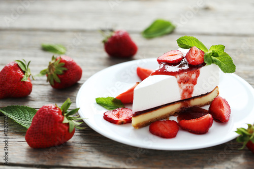 obraz lub plakat Strawberry cheesecake on plate on grey wooden table