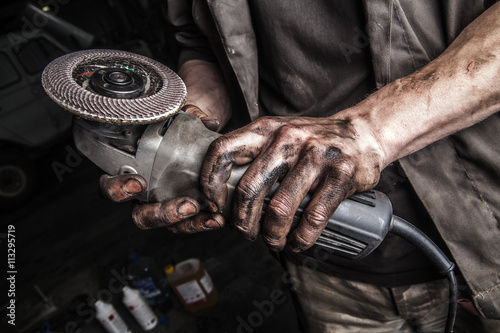 Poster Dirty hands with angle grinder