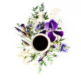 Cup of coffee with purple iris and lily of the valley flowers. Flat lay, top view