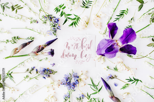 """Poster inspirational quote """"work hard dream big"""" written in calligraphy style on paper with wreath frame with purple iris flower and lilies isolated on white background"""