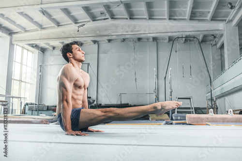 Poster caucasian man gymnastic acrobatics equilibrium posture at gym background
