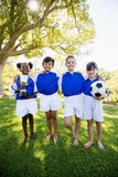Portrait of children soccer team in raw smiling