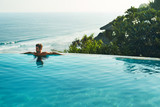 Luxury Resort. Man Relaxing In Infinity Swimming Pool Water. Beautiful Happy Healthy Male Model Enjoying Summer Travel Vacation At Tropical Spa Hotel In Indonesia, Sea View. Summertime Relax Concept