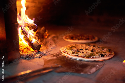 raw pizza lay down stove with the fire on blade.