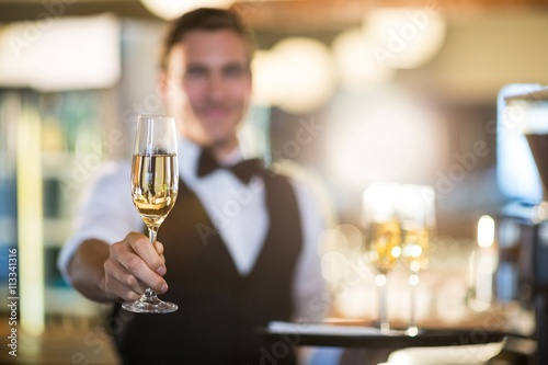 Fotografiet Waiter offering a glass of champagne
