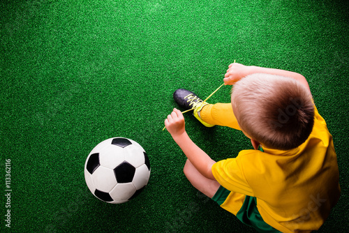 Unrecognizable little football player against green grass, studi