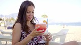 Happy friendly young woman drinking a tropical cocktail as she sits at an open air beachfront restaurant relaxing on her summer vacation