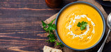 Fototapety Pumpkin and carrot soup with cream and parsley on dark wooden background Top view Copy space