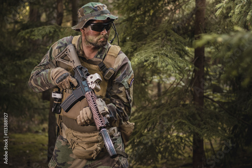 Fototapeta soldier with a rifle in the woods