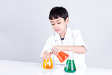 Asian boy doing science experiment with color liquid