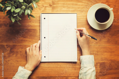 Hands of a person writing in a small notepad