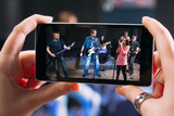 Music band performance photographing on smartphone. Closeup of smartphone screen with picture of young student rock band performance in sound recording studio
