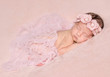 newborn cute girl sleeping on a pink background