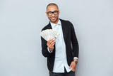 Cheerful african american young man standing and holding money