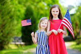 Two adorable little sisters holding american flags outdoors on beautiful summer day