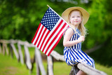 Adorable little girl wearing hat holding american flag outdoors on beautiful summer day