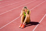 Upset female athlete sitting on running track