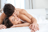 Young couple in love on the bed in bedroom