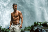 Fototapety Water Drink. Healthy Man With Sexy Fit Body Holding Bottle Of Fresh Pure Water, Enjoying Nature Near Beautiful Tropical Paradise Waterfall On Summer Travel Vacation. Health Care, Hydration Concept