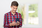young casual man texting onhis smartphone