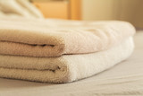 stack of towels on bed in bedroom