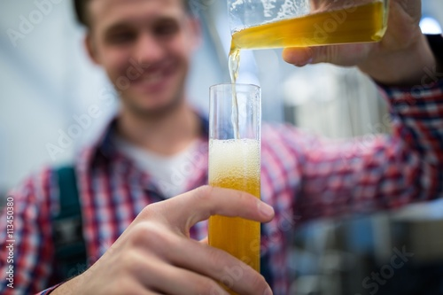 Brewer pouring beer in hydrometer cylinder Poster