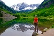 Woman Standing by Lake with Mountains View and Reflection. Maroon Bells near Aspen and Snowmass Village, Colorado State, USA.