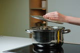 Female hand holding the lid of the pan. Person removing lid from cooking pot.