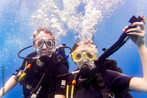 obraz lub plakat Mann und Frau beim Tauchen im tropischen Meer steigen wieder auf nach Tauchgang