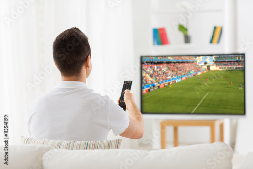 man watching football or soccer game on tv at home